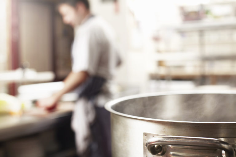 Pot of water in kitchen with chef in the background