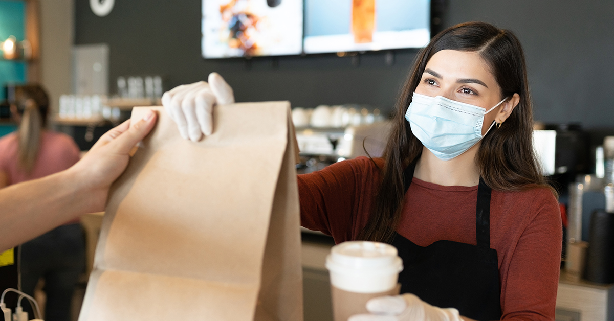 woman wearing mask giving bag and coffee to customer
